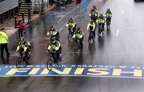Police on bikes cycle across the Boston Marathon finish line prior to a remembrance ceremony for family members and survivors of the 2013 Boston Marathon bombing on Boylston Street in Boston, Tuesday, April 15, 2014.