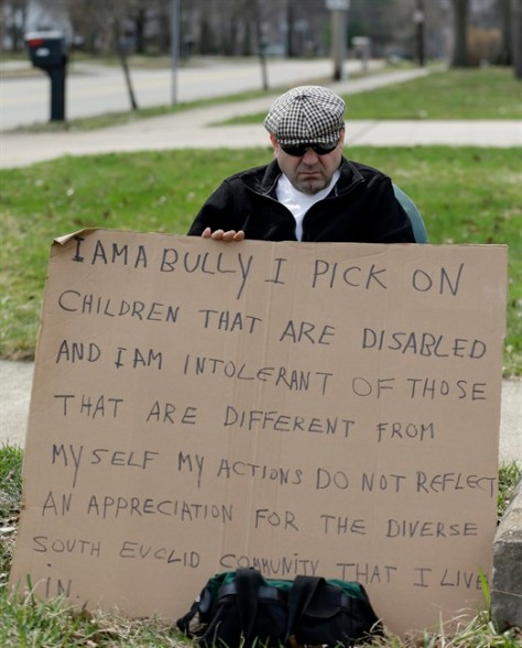 Edmond Aviv sits on a street corner holding a sign Sunday, April 13, 2014, in South Euclid, Ohio declaring he's a bully, a requirement of his sentence because he was accused of harassing a neighbor and her disabled children for the past 15 years.