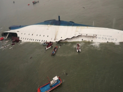 In this photo released by South Korea Coast Guard via Yonhap News Agency, South Korean rescue team boats and fishing boats try to rescue passengers of a ferry sinking off South Korea's southern coast, in the water off the southern coast near Jindo, south of Seoul, Wednesday, April 16, 2014.