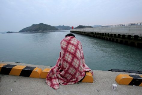 A relative waits for their missing loved one at a port in Jindo, South Korea, Wednesday, April 16, 2014.