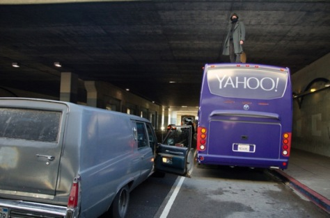 A hearse rolls up to a Yahoo bus at the BART MacArthur Station in Oakland. A protester who had climbed on top of the bus later vomited on the vehicle. (From Indybay)